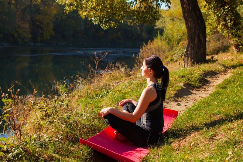 Situação de relaxamento da jovem mulher na pose dos lótus perto do rio fotos de stock
