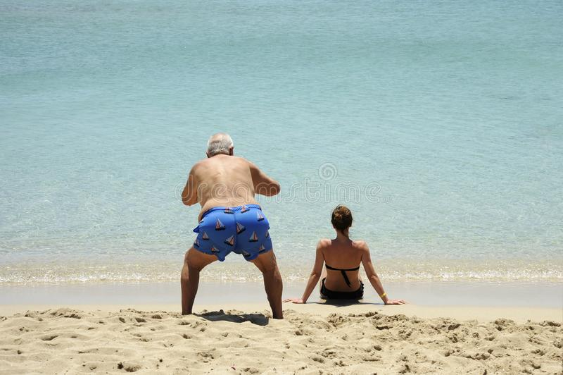 Situação engraçada e cômica Um idoso tira fotos de uma linda garota sentada na praia imagens de stock