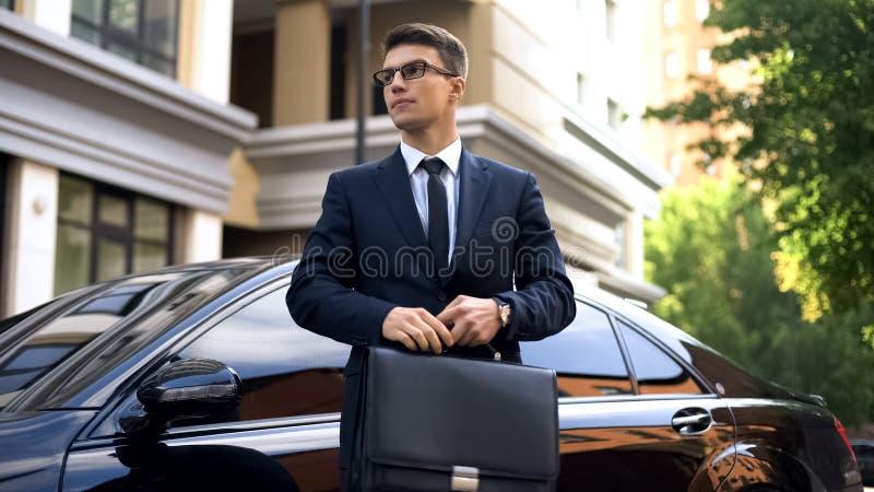 Situación acertada cerca del coche de lujo, asistencia social, seguro del hombre de negocios de vida imagen de archivo