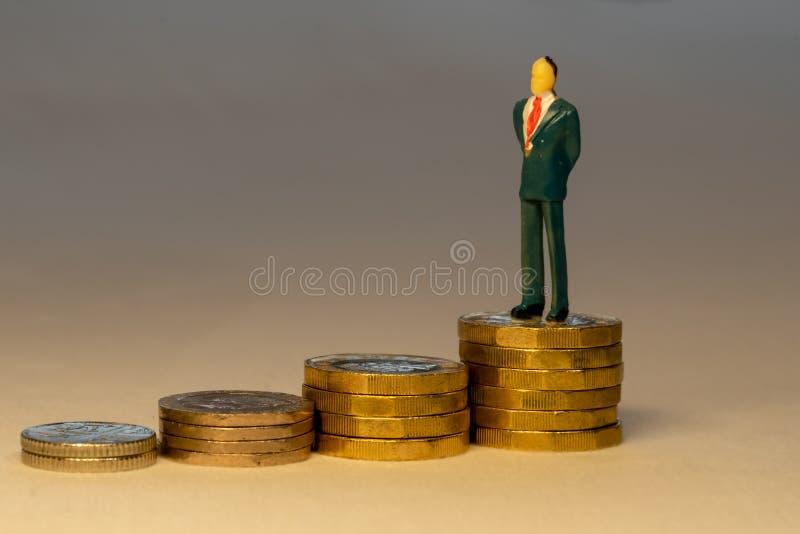 Situación acertada rica del hombre de negocios encima de pilas cada vez mayores de monedas de oro Concepto de la carrera del nego imágenes de archivo libres de regalías