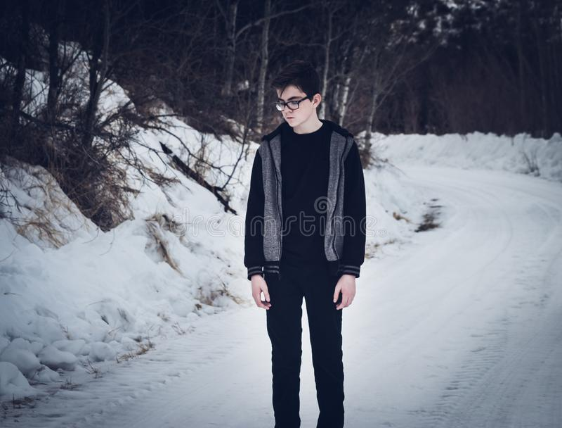 Situación adolescente del muchacho en un camino nevado imagen de archivo libre de regalías