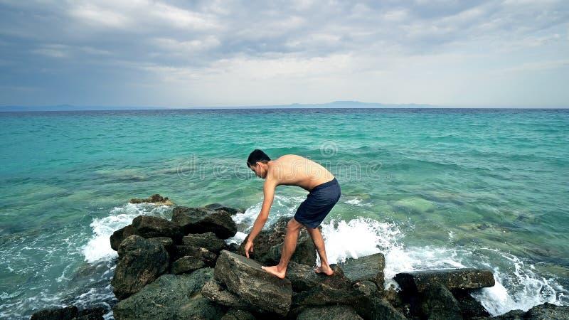 Situación adolescente masculina sola perdida en roca del mar foto de archivo libre de regalías