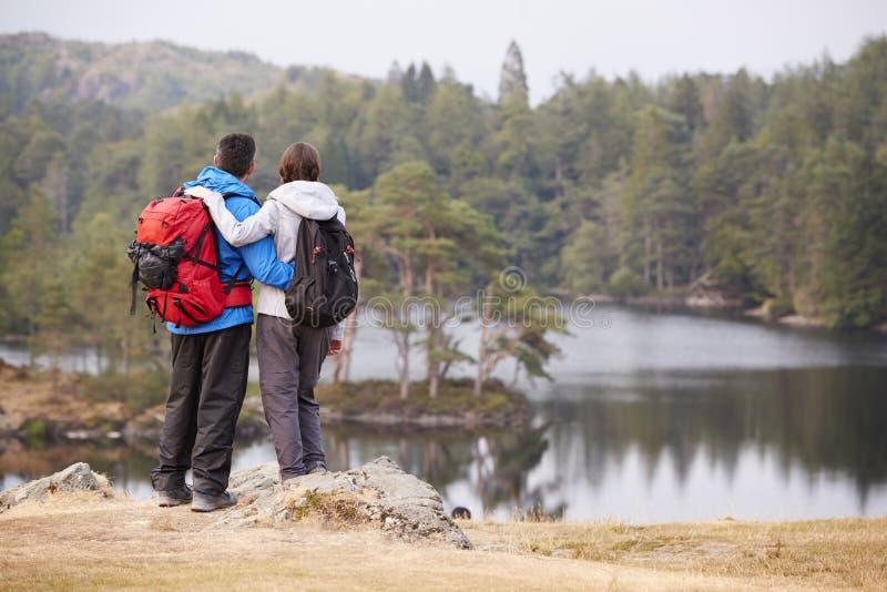 Situación adulta joven de los pares en una roca que admira la opinión de la orilla del lago, visión trasera foto de archivo