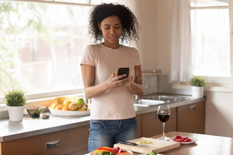 Situación africana de la mujer en la cocina distraída de cocinar usando el teléfono móvil imagen de archivo libre de regalías