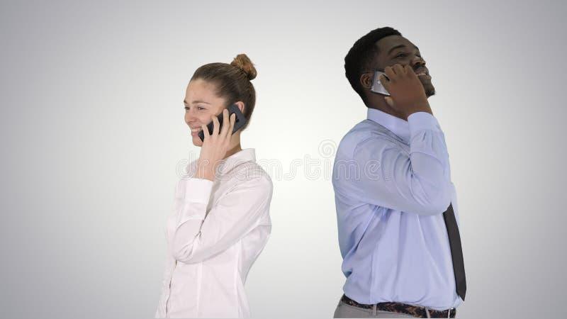 Situación afroamericana joven del hombre y de la mujer de nuevo a la parte posterior que hace llamadas de teléfono en fondo de la fotografía de archivo libre de regalías