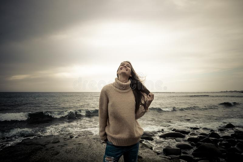 Situación alegre del bebé en la playa en una roca salvaje con las ondas y el horizonte del agua azul en el fondo Concepto de la f foto de archivo libre de regalías