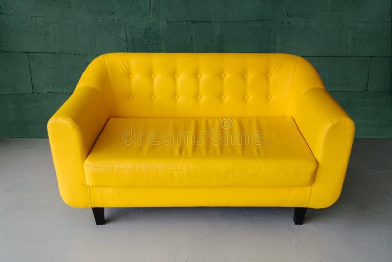 Situación amarilla elegante del sofá en el cuarto fotos de archivo