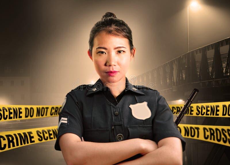 Situación americana asiática joven del oficial de policía seria en la custodia de la escena del crimen para preservar pruebas en  imagen de archivo libre de regalías