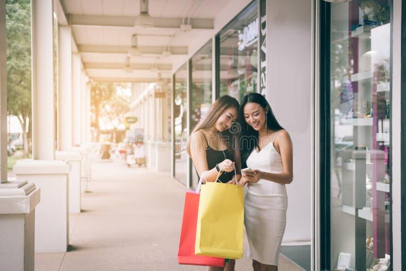 Situación asiática de la mujer dos en el frente de la tienda con el teléfono elegante de observación feliz en el centro del centr foto de archivo