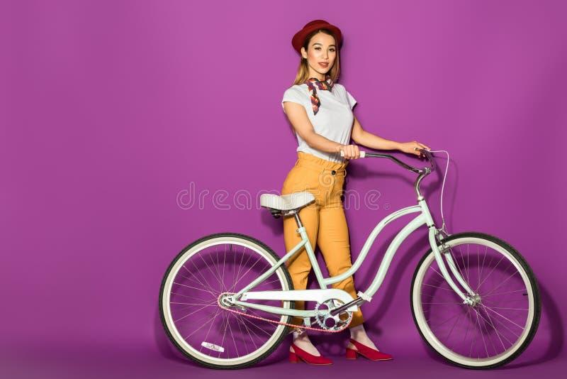 situación asiática elegante hermosa de la muchacha con la bici y sonrisa en la cámara imagenes de archivo