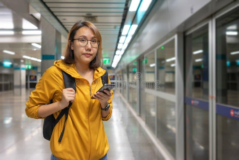 Situación asiática hermosa de la mujer del retrato que sostiene un smartphone que espera el subterráneo en Tailandia para el viaj fotos de archivo libres de regalías