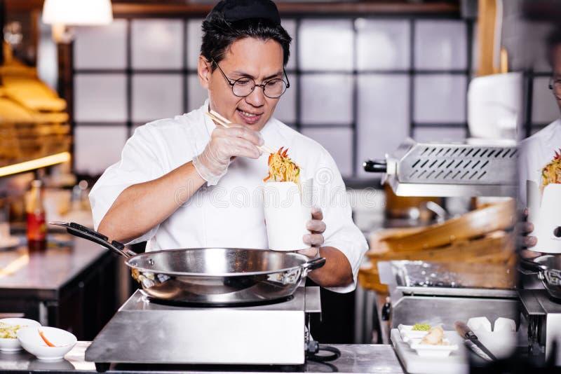 Situación asiática impresionante del cocinero delante del sartén y de la orden de la preparación fotografía de archivo libre de regalías