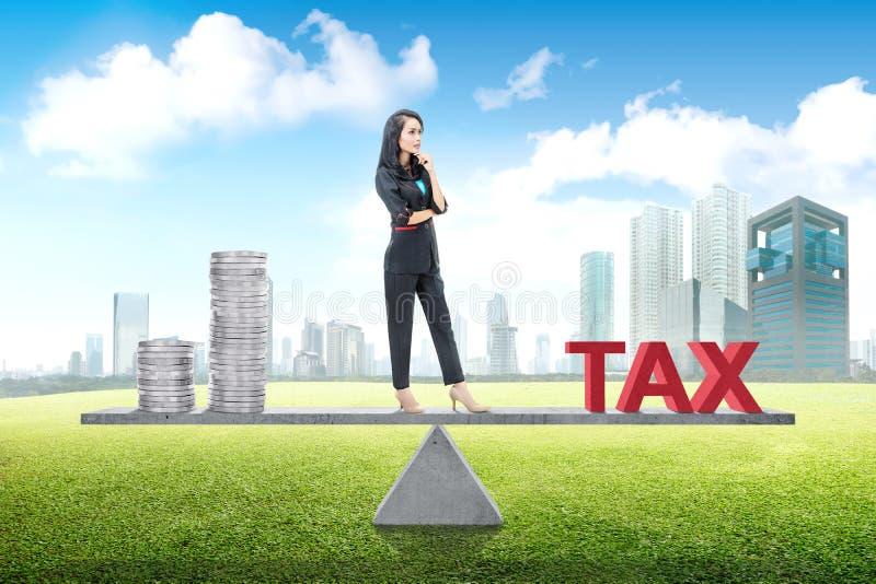 Situación asiática joven de la mujer de negocios equilibrio entre la renta y el impuesto imágenes de archivo libres de regalías
