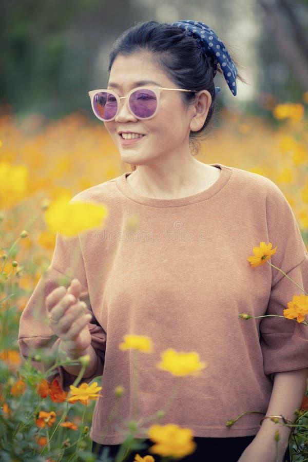 Situación asiática sonriente de la mujer de la cara del retrato con la emoción de la felicidad en campo floreciente del cosmos am foto de archivo libre de regalías