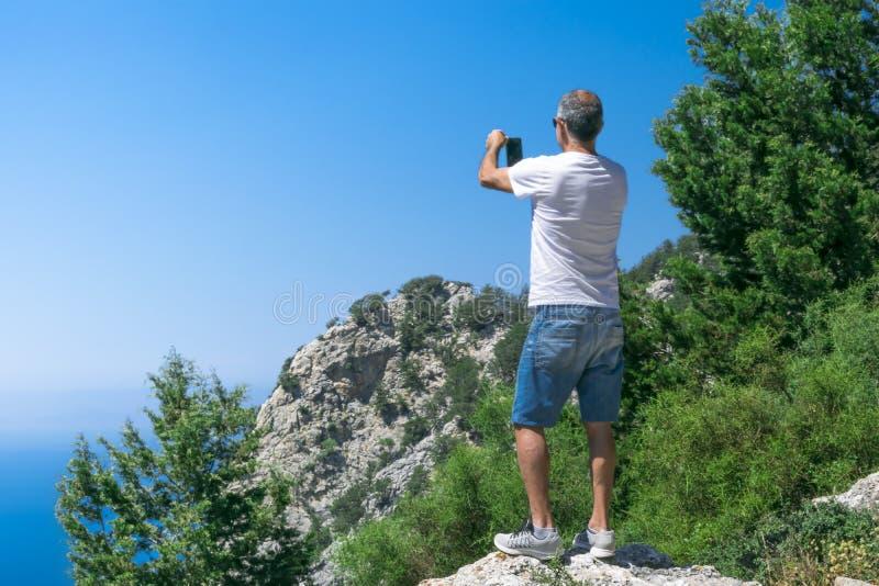 Situaci?n atl?tica adulta del hombre en el top de la monta?a y tomar una foto de la naturaleza hermosa usando un smartphone conce fotografía de archivo