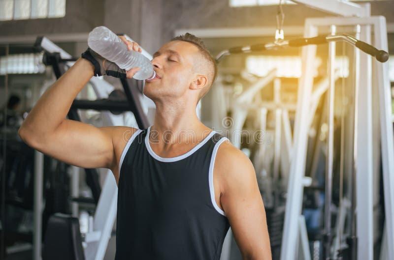 Situación atractiva del hombre fuerte y agua potable en gimnasio, la rotura masculina y el relex después del entrenamiento, conce fotos de archivo