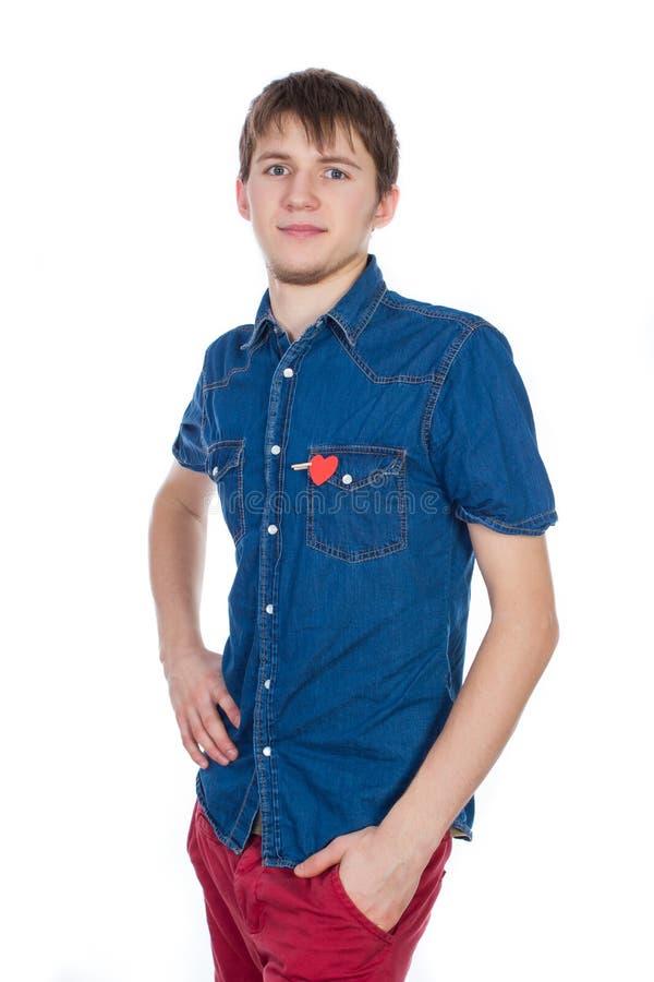 Situación atractiva del muchacho aislada en el fondo blanco con un corazón de papel rojo en su bolsillo fotografía de archivo