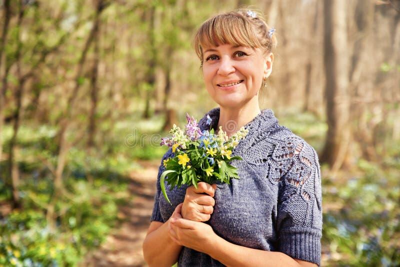 Situación atractiva hermosa de la mujer en el bosque y disfrutar de la naturaleza Mujer adulta preciosa con un ramo de flores imagen de archivo libre de regalías