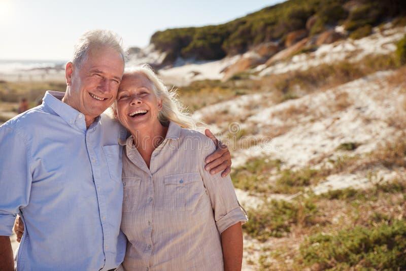 Situación blanca mayor de los pares en una playa que abraza y que sonríe a la cámara, cierre para arriba imagen de archivo