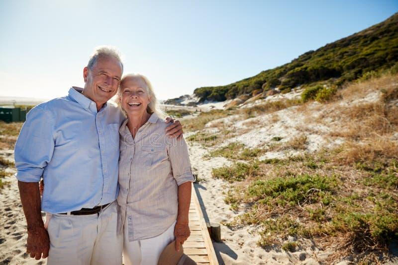 Situación blanca mayor de los pares en una playa que abraza y que sonríe a la cámara, longitud del tres cuartos imagen de archivo