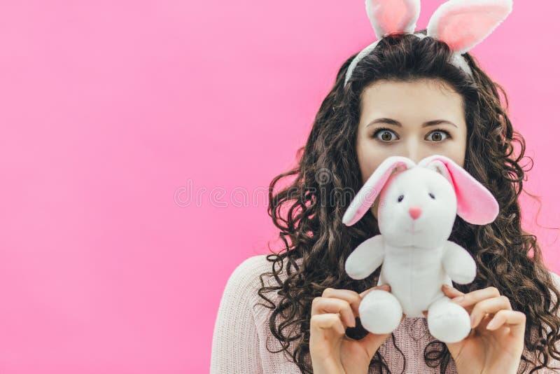 Situación bonita joven de la muchacha en un fondo rosado En el jefe de los oídos del conejito Durante esto, él lleva a cabo una s fotos de archivo