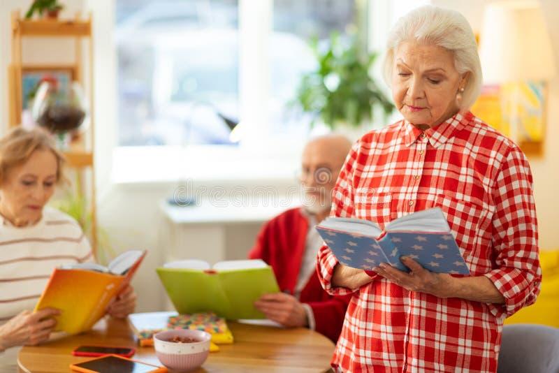 Situación cabelluda gris seria de la mujer con un libro imagenes de archivo