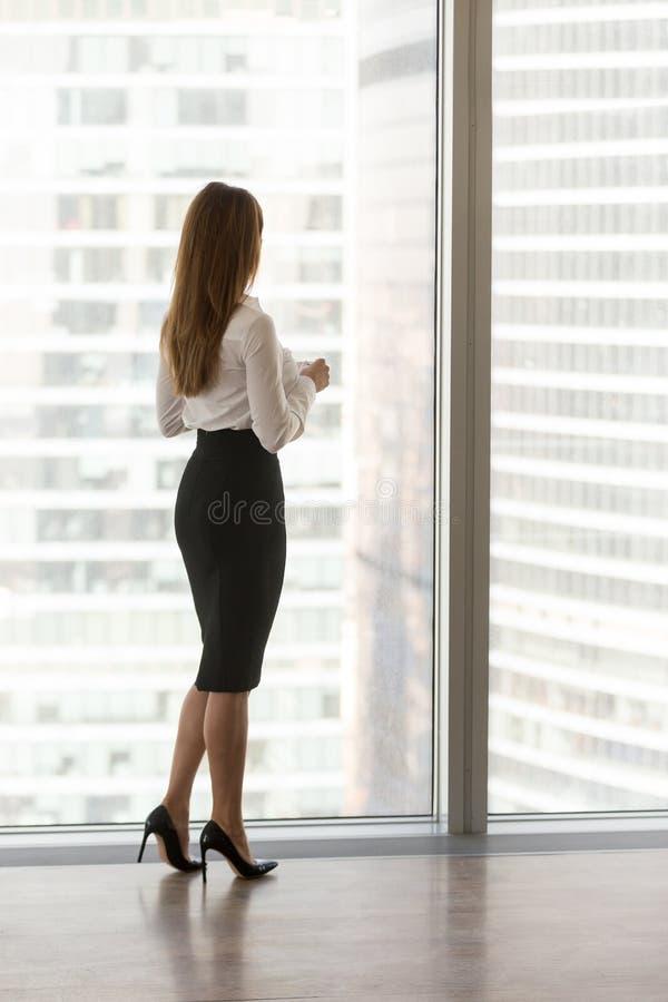 Situación confiada en la ventana de la oficina, vertical posterior de la empresaria fotografía de archivo