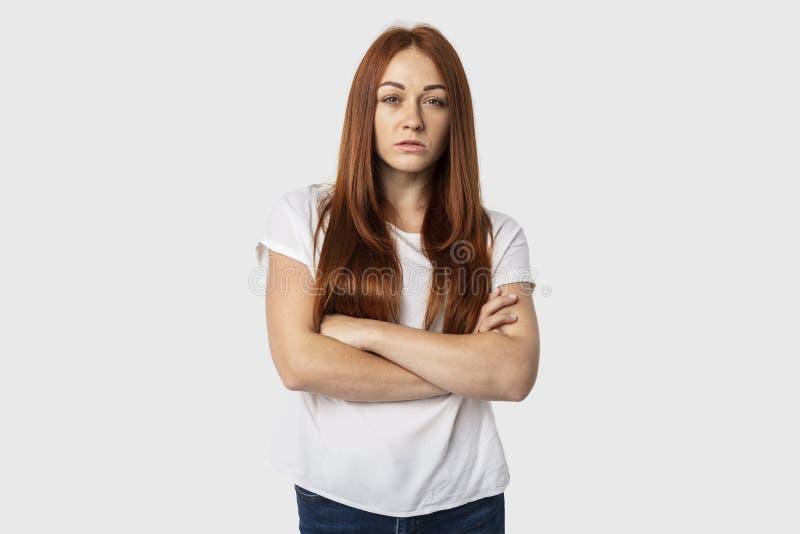 Situación de la chica joven con los brazos cruzados aislados en fondo gris con una mirada seria imagen de archivo