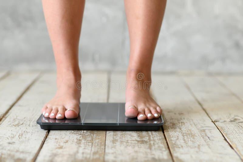Situación de la muchacha en escalas Positivo del cuerpo Tama?o m?s foto de archivo