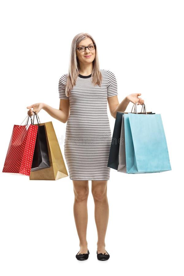 Situación de la mujer con los bolsos de compras y sonrisa en la cámara foto de archivo