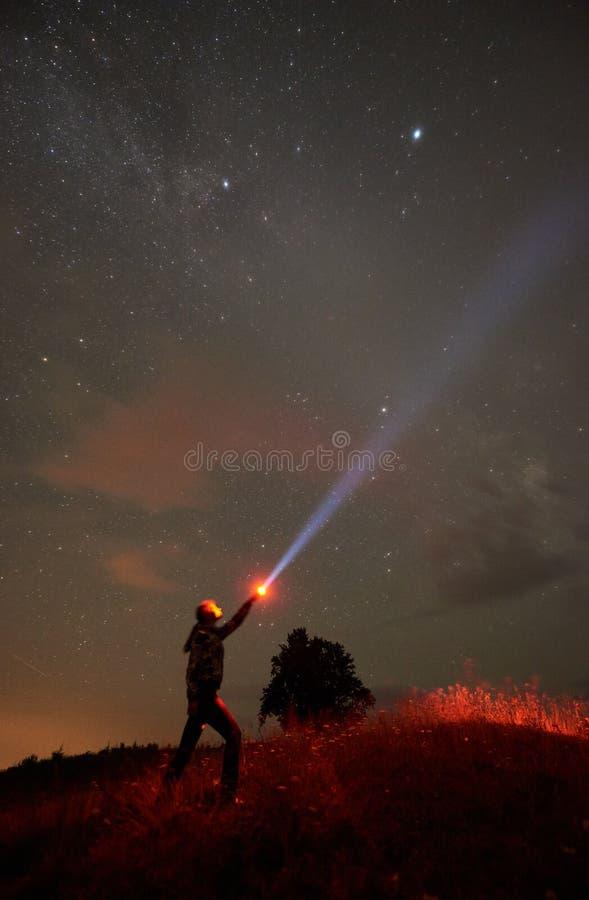 Situación de la mujer contra el cielo estrellado de la noche en las montañas con una linterna en su mano foto de archivo