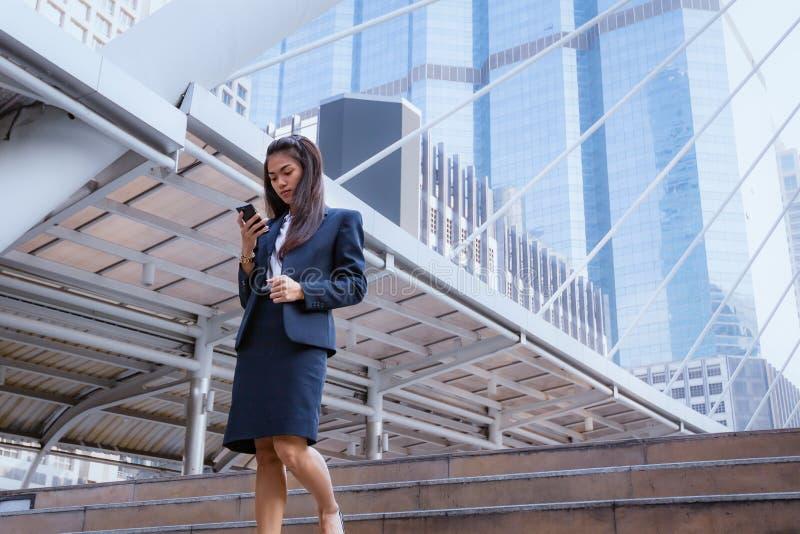 Situación de la mujer de negocios y smartphone asiáticos del uso con el negocio b imagenes de archivo