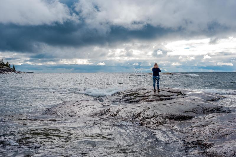 Situación de la mujer en orilla rocosa con estrellarse de las ondas fotografía de archivo libre de regalías