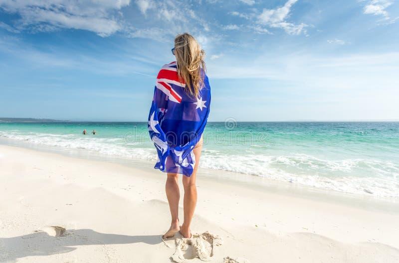 Situación de la mujer en la playa con la bandera envuelta alrededor de ella fotos de archivo libres de regalías