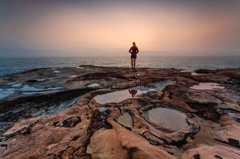 Situación de la mujer en rocas de la piedra arenisca con salida del sol costera de niebla imagenes de archivo