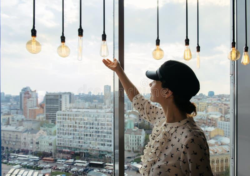Situación de la mujer joven cerca de la ventana que disfruta de horizonte de la ciudad fotos de archivo