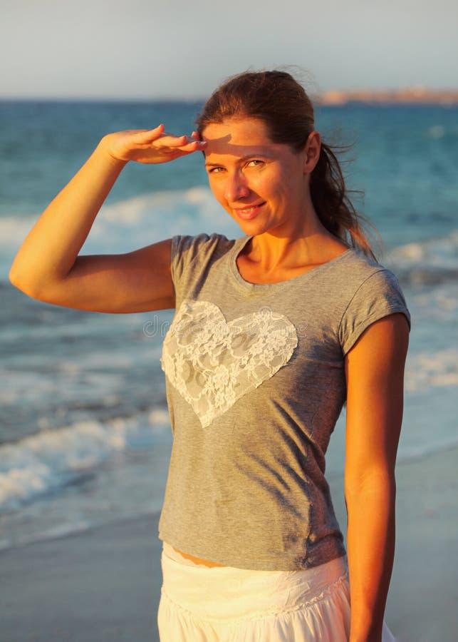 Situación de la mujer joven en la playa, sombreando sus ojos de luz del sol durante puesta del sol, mar detrás de ella imagen de archivo libre de regalías