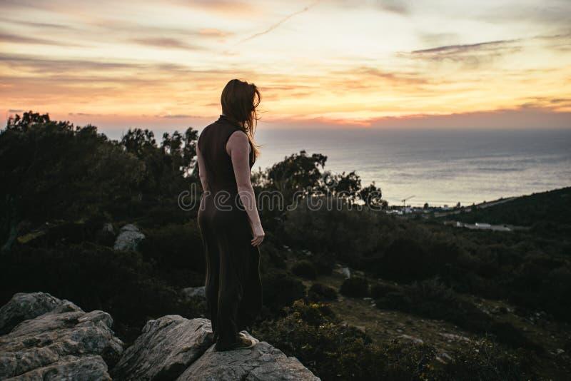 Situación de la mujer joven en un afloramiento rocoso en la puesta del sol imagen de archivo
