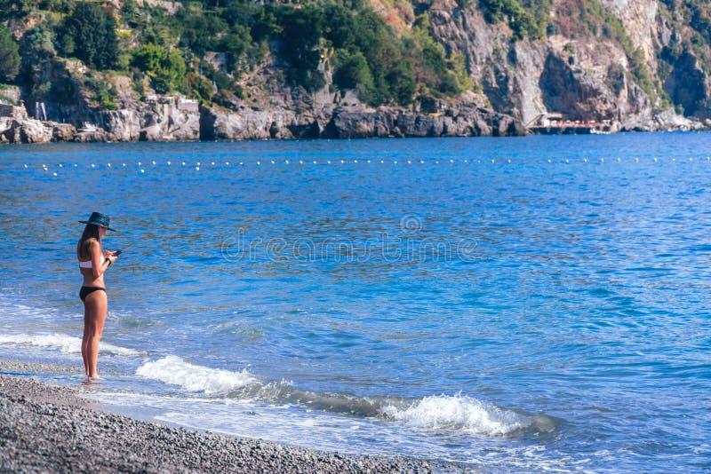 Situación de la mujer joven solamente en la playa y la mirada en su teléfono Concepto bueno, mala señal fotografía de archivo libre de regalías