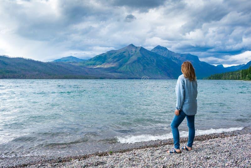Situación de la mujer a lo largo de la orilla del lago que admira las montañas imagen de archivo