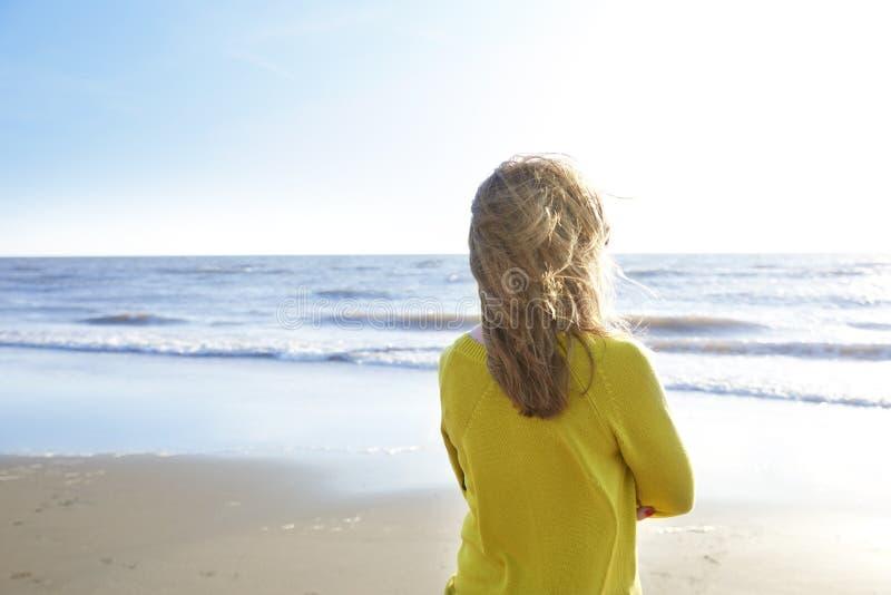 Situación de la mujer sola en la playa y la mirada del mar imagenes de archivo