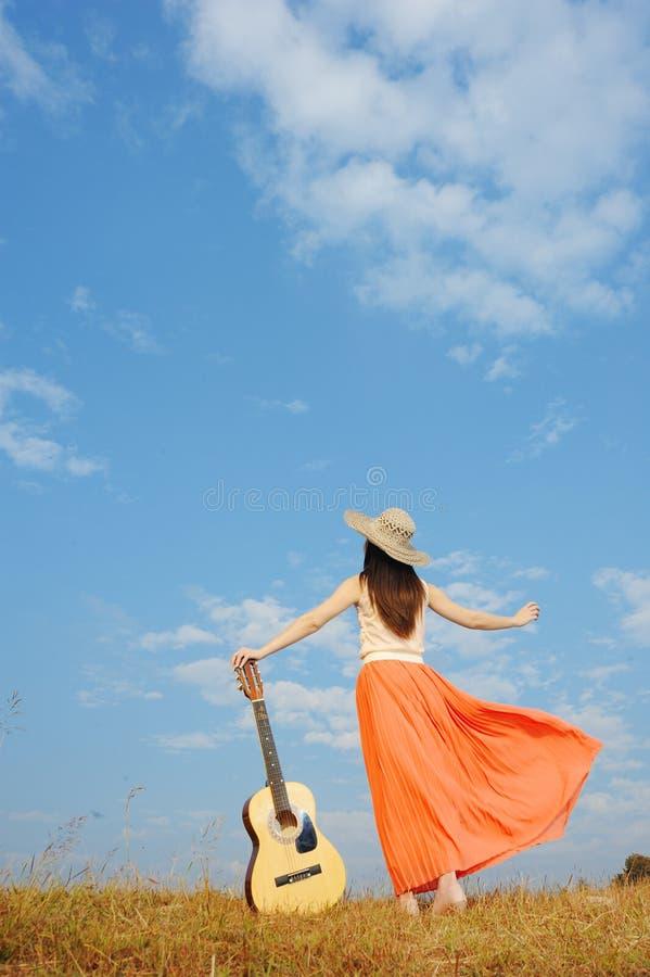 Situación de la mujer y de la guitarra y cielo de la nube imagenes de archivo