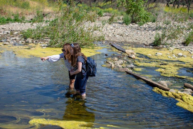 Situación de la mujer y de la hija y agua el señalar mientras que se coloca en una corriente o un río imágenes de archivo libres de regalías