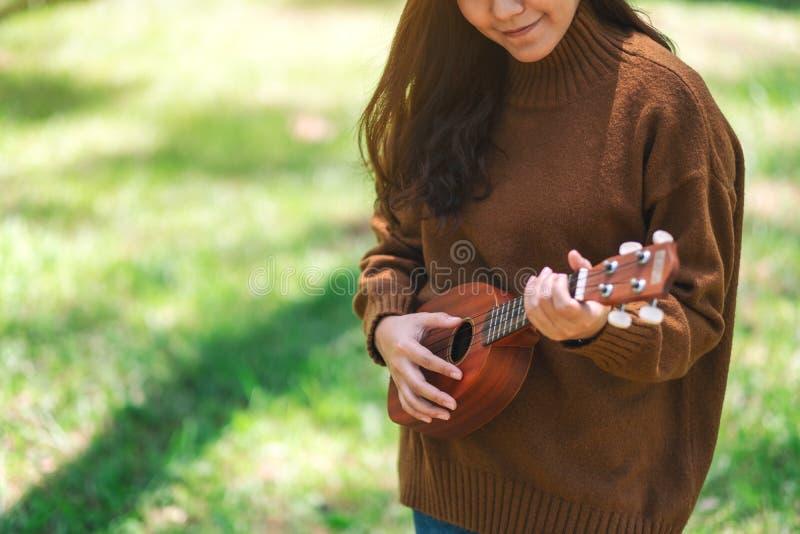 Situación de la mujer y ukelele el jugar en el parque foto de archivo libre de regalías