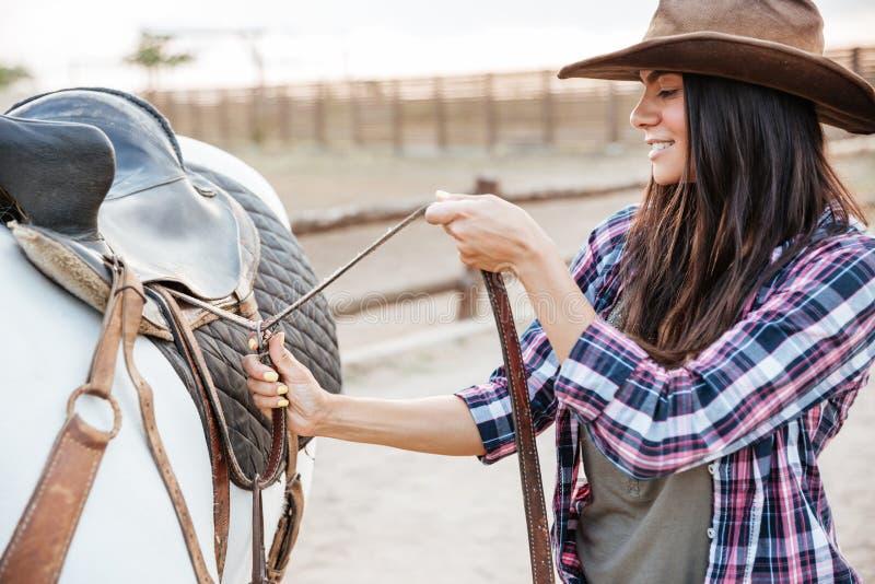 Situación de la vaquera de la mujer y silla de montar el poner en caballo imágenes de archivo libres de regalías