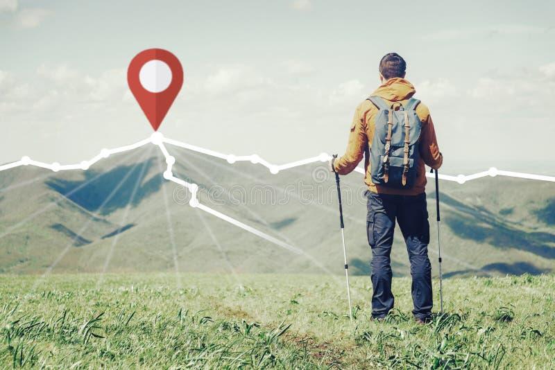 Situación del caminante delante del perno de GPS en el pico de la montaña imágenes de archivo libres de regalías