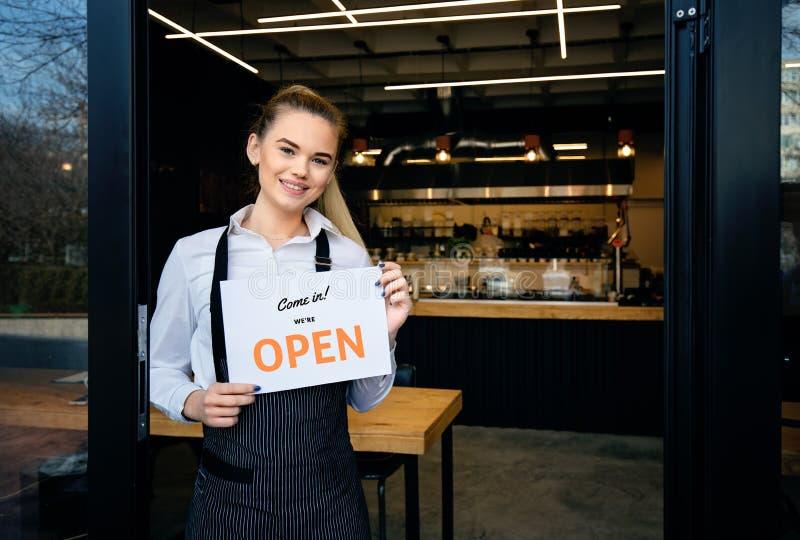 Situación del delantal de la camarera que lleva en la entrada del restaurante La mujer asiste a nuevos clientes en su cafetería D fotos de archivo