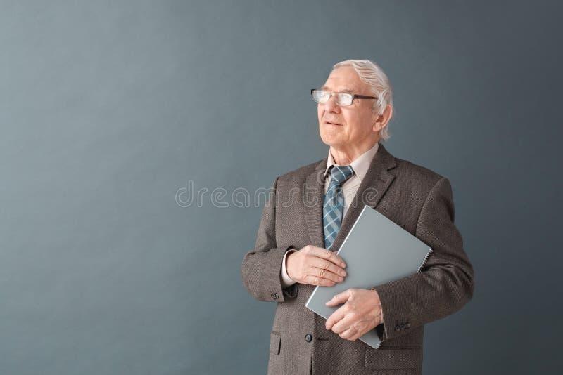 Situación del estudio de los vidrios del profesor del hombre que lleva mayor aislada en el libro que se sostiene gris que parece  foto de archivo libre de regalías