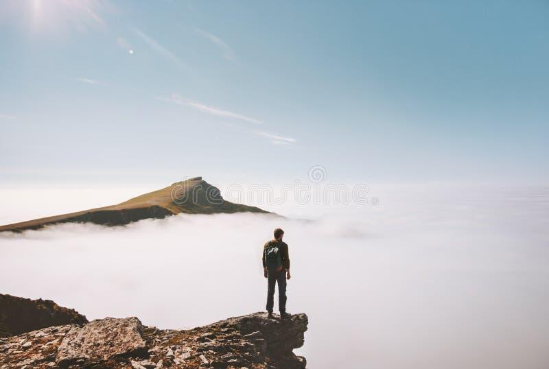 Situación del explorador del hombre sola en la montaña del borde del acantilado sobre las nubes imagen de archivo libre de regalías