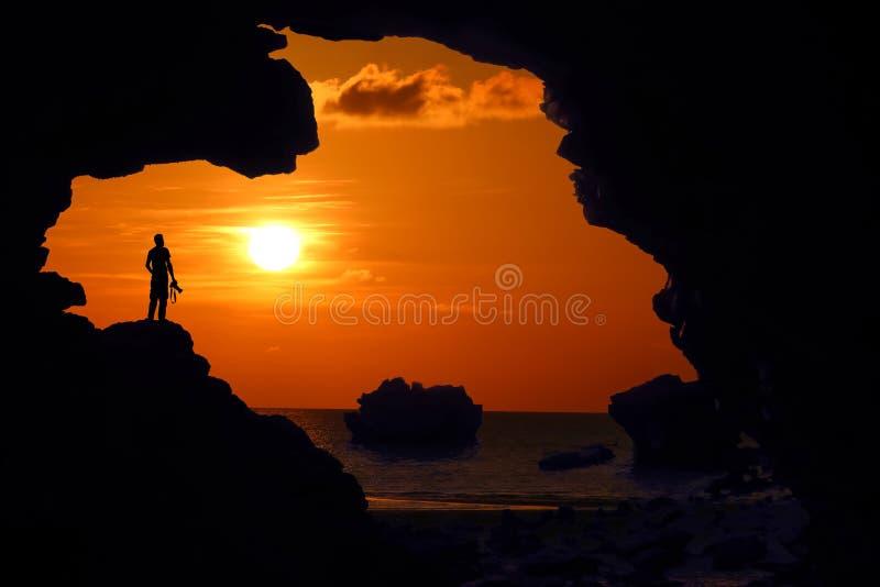 Situación del fotógrafo en la cueva cerca de la playa en la puesta del sol roja del cielo imagen de archivo libre de regalías